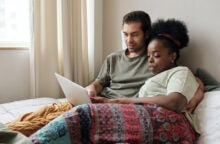 A young couple sits in bed on a laptop discussing savvy money moves.